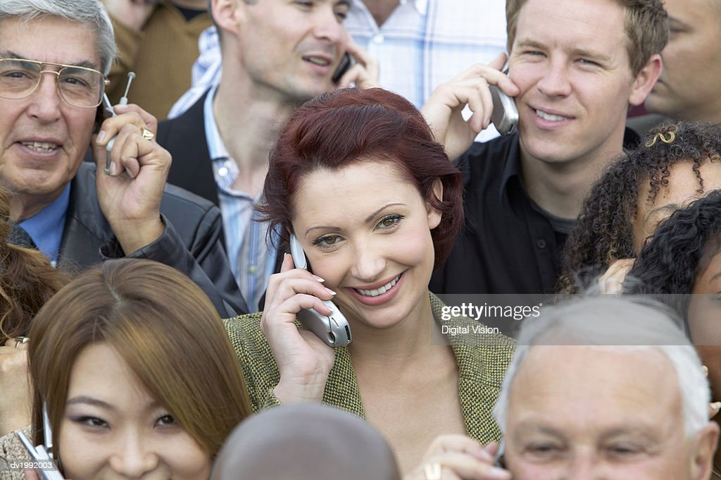 Focus on a Woman in a Large Crowd Using Mobile Phones : Stock Photo