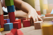 Focus on child's hand  playing with colorful wooden blocks in vintage color tone
