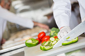 Focus on knife chopping vegetables in commercial kitchen