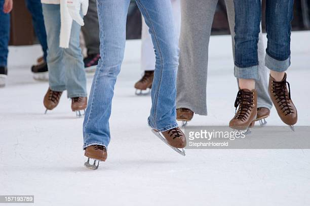 Focus on legs and skates of ice skating people