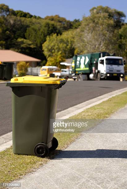 Focus on Rubbish bin with rubbish truck approaching bins