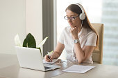 Focused attentive woman in headphones sits at desk with laptop, looks at screen, makes notes, learns foreign language in internet, online study course, self-education on web, consults client by video