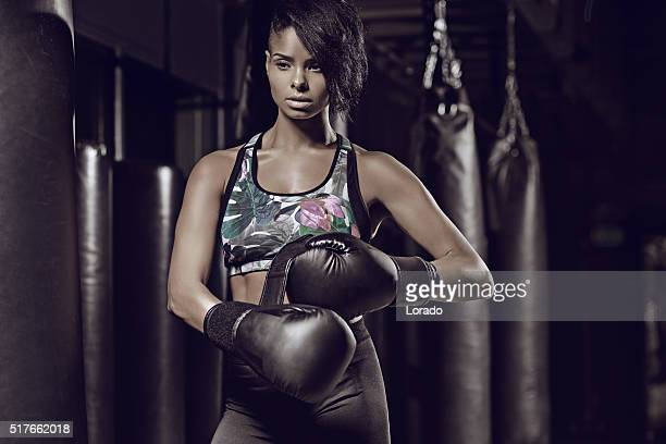 Focused dark haired female preparing at boxing gym