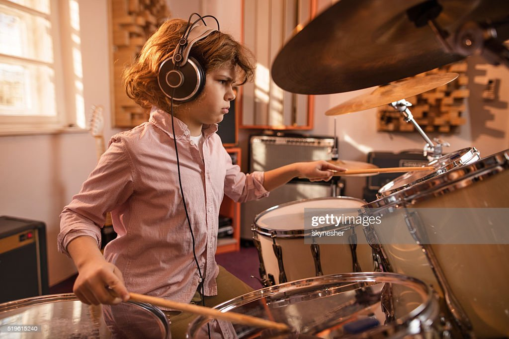 Focused little boy playing drums in music studio. : Stock Photo