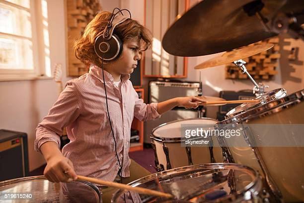 Focused little boy playing drums in music studio.