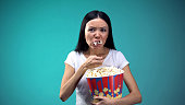 Focused on movie woman devouring popcorn from big paper cup, unhealthy eating