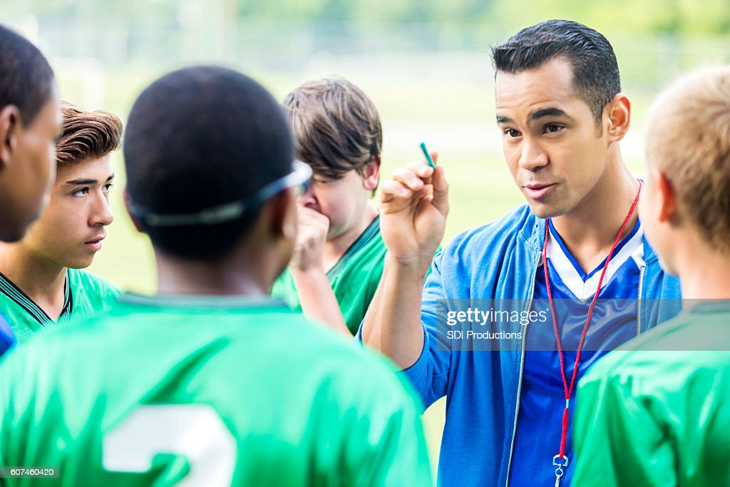 Focused soccer coach gives players a pep talk : Stock Photo