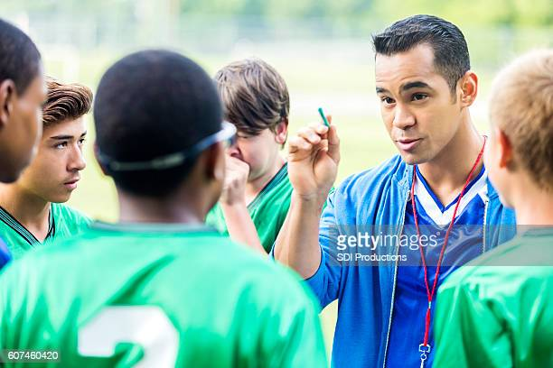 Focused soccer coach gives players a pep talk
