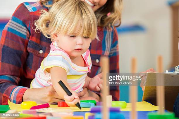 Focused toddler girl working on school project