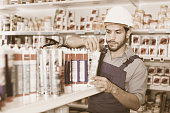 Focused  positive  workman choosing materials for renovation works in paint store