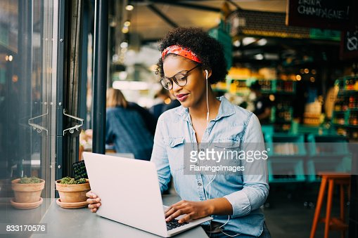 Focused young African woman working online in a cafe : Stock Photo