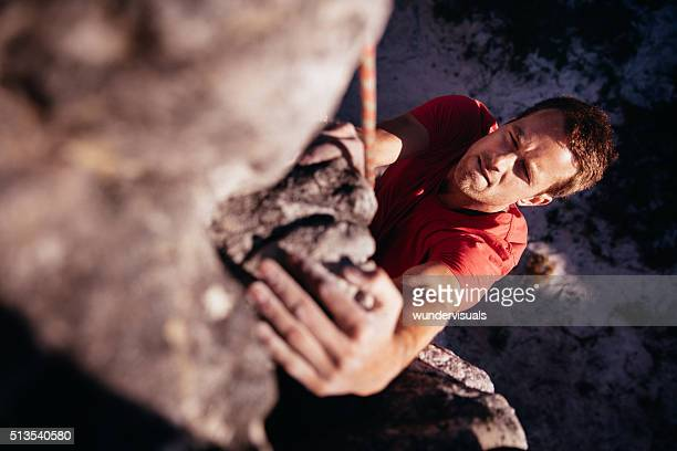 Focussed Rock climber holding on grip while hanging from boulder