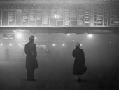 Two passengers looking at the train departure board at Liverpool Street Station London during heavy fog 29th January 1959 Most rail services have...