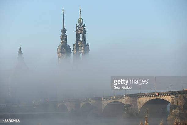Fog rising from the Elbe River shrouds landmarks in the city center including August Bridge and towers of the Residenzschloss Dresden palace and the...