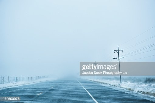Fog rolling over snowy rural road