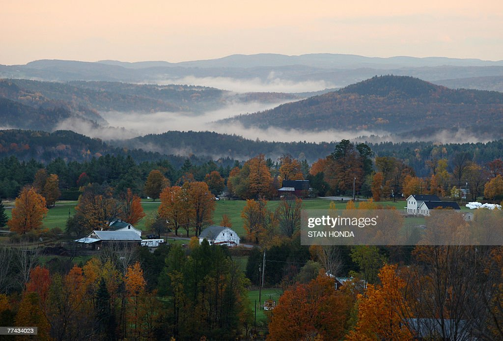 Fog settles between hills at daybreak as leaves show their fall colors 20 October 2007 in this view from the Comstock House bed breakfast/farm in...