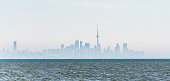 Distant city skyline silhouette of Toronto downtown in fog and mist with wavy water of Lake Ontario in foreground.