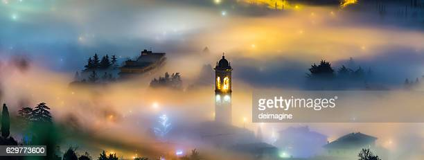 Foggy landscape over a country with bell tower