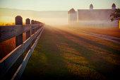 Foggy morning farm fence at sunrise