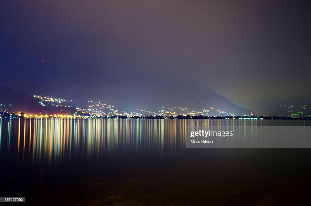 Foggy night with lights on alpine lake