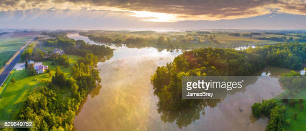 Foggy river reflecting sky under Summer sunrise, panoramic aerial view