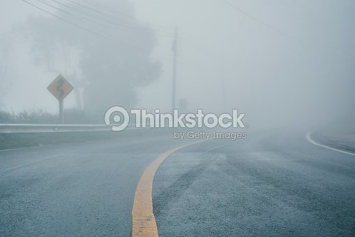 foggy rural asphalt highway perspective with white line, misty road, Road with traffic and heavy fog, bad weather driving : Foto de stock