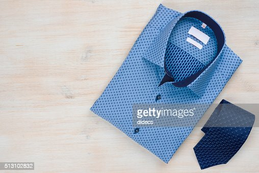 Folded blue man shirt and tie isolated on wooden background : Stock Photo