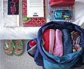 Folded clothes in open rucksack, beside belongings piled neatly on bed