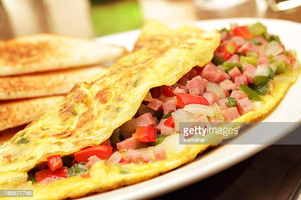 A folded egg omelets filled with chopped ham and vegetables