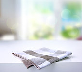 Folded checkered grey brown kitchen towel cloth on white table empty advertisement space.