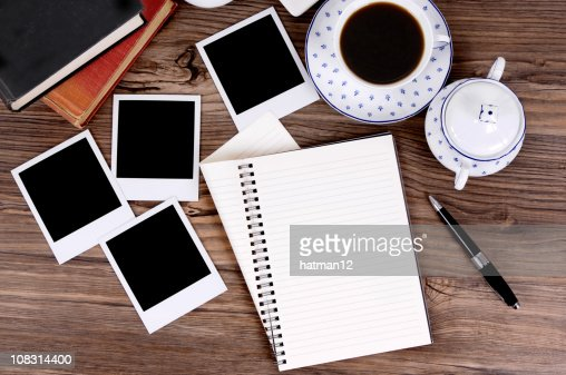 Folded spiral notebook with coffee and photo prints : Stock Photo
