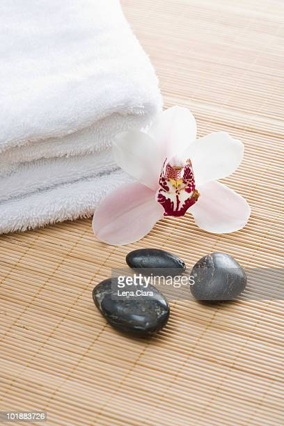 Folded towels, Lastone therapy stones and an orchid arranged on a Tatami mat