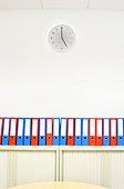 Folders lined on shelf, clock on wall, low angle view
