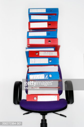 Folders stacked on office chair : Stock Photo