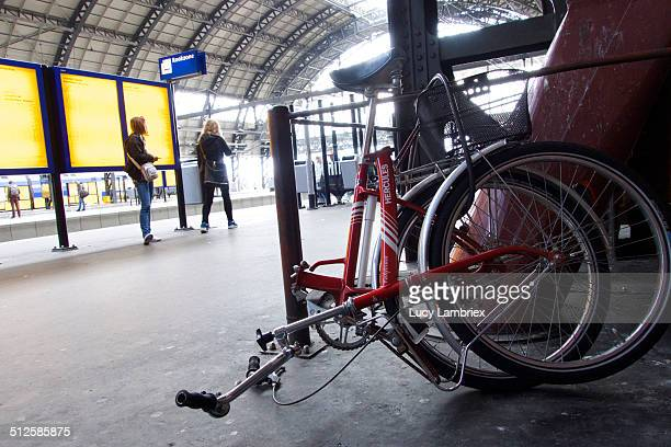 Folding bike at Amsterdam Central station chained to a railing on platform 2