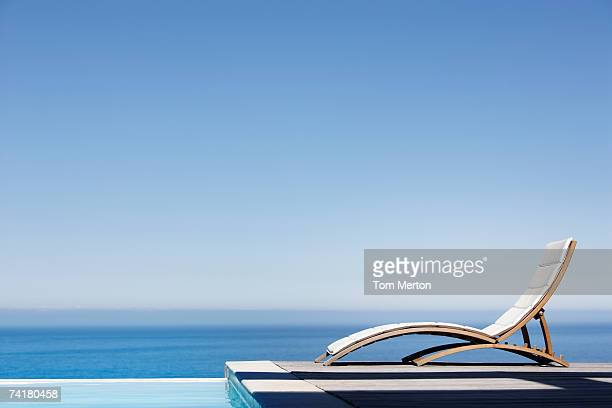 Folding chair on deck with infinity pool
