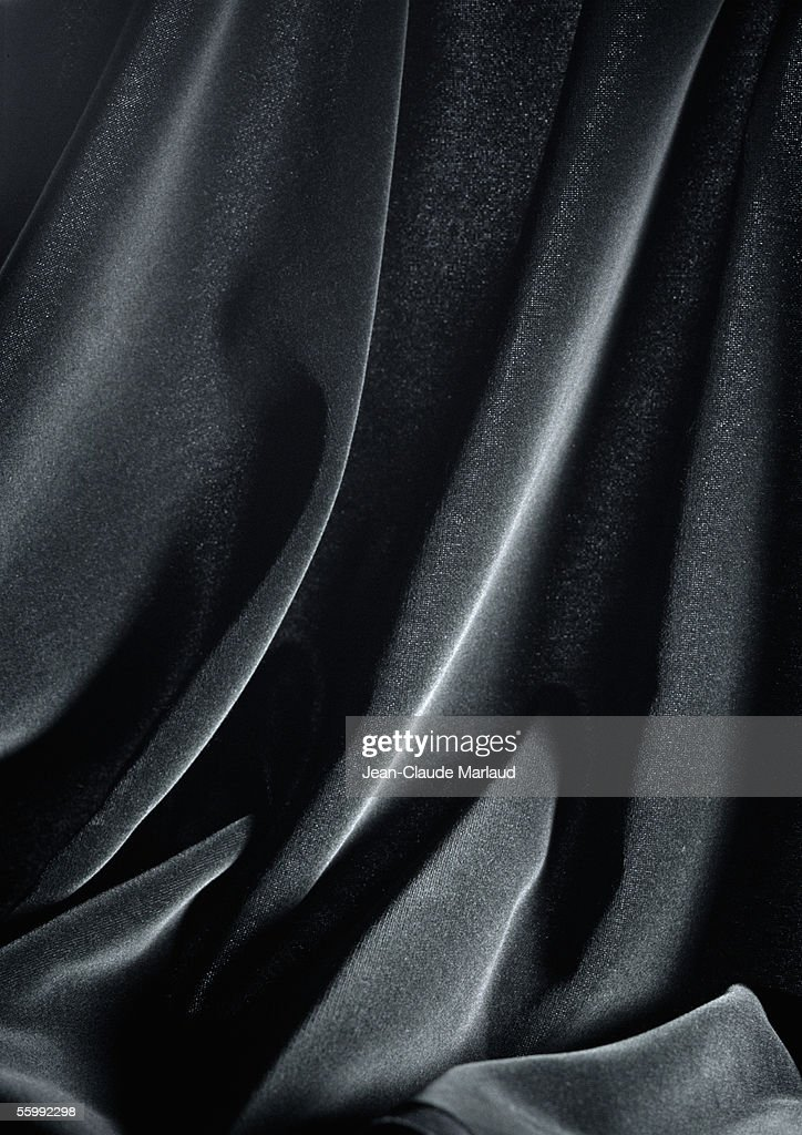 Folds in shiny black fabric, close-up, full frame