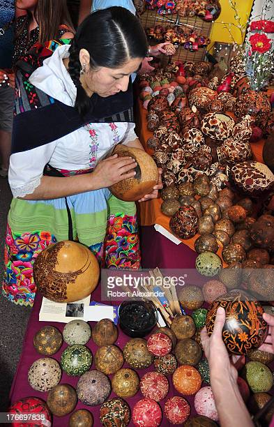 Folk artist Bertha Aquino from Peru embellishes the designs carved into a gourd with wet powdered charcoal at the International Folk Art Market in...