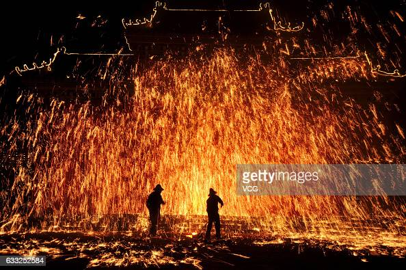 Folk artists perform molten iron fireworks at a scenic area in Neihuang County to celebrate the Lunar New Year on January 31 2017 in Anyang Henan...