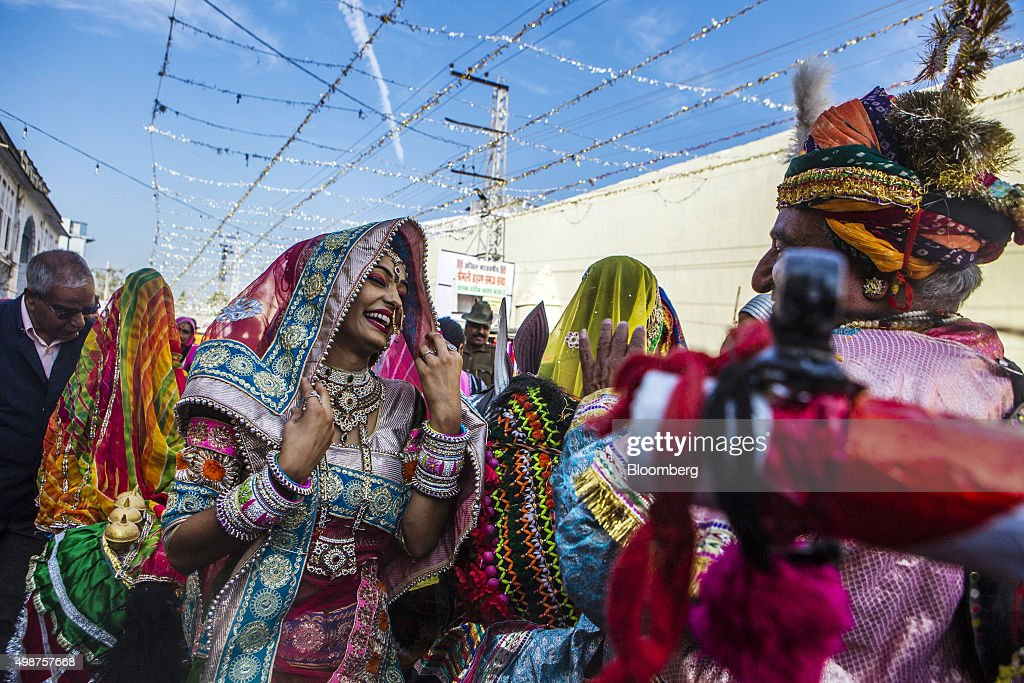A folk dancer reacts as she participates in a procession showcasing artists and children dressed as various Gods and Godesses through a street during...