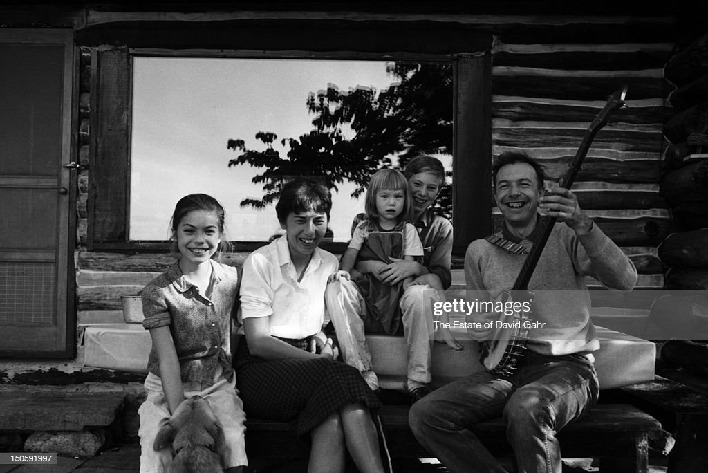 Folk musician Pete Seeger poses for a portrait with his family (l-r: Mika Seeger, wife and partner Toshi Seeger, Tinya Seeger, Daniel Seeger, Pete Seeger) at their log cabin home in August, 1958 in Beacon, New York.