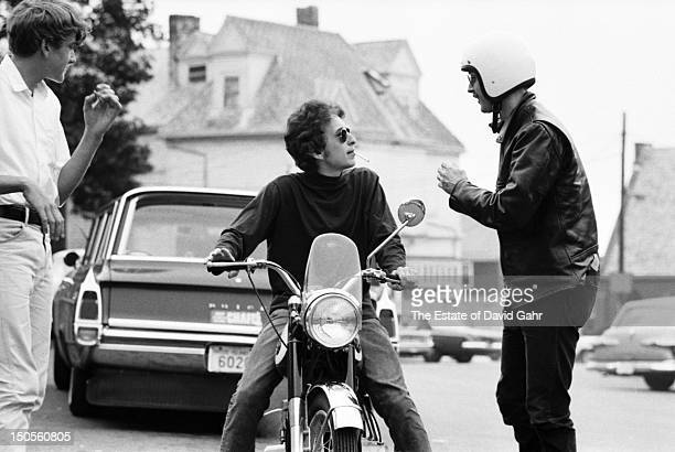 Folk singer Bob Dylan confers with a friend while sitting atop a motorcycle before a performance at the Newport Folk Festival in July 1964 in Newport...