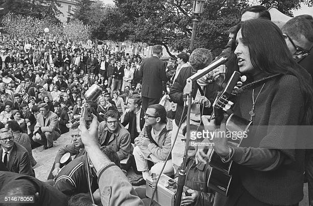 Folk singer Joan Baez sings and plays her guitar in front of a crowd at a freedom rally in front of Sproul Hall at the University of California...