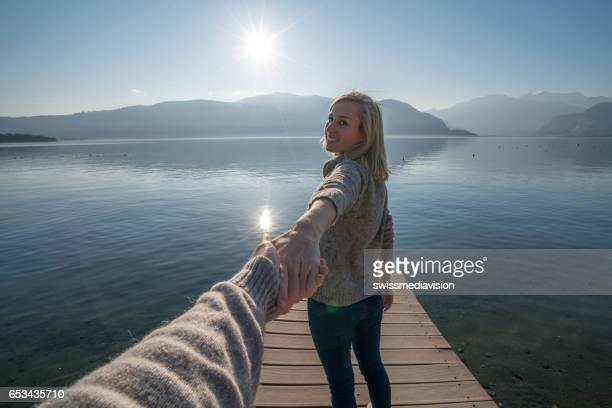 Follow me concept- woman on lake pier