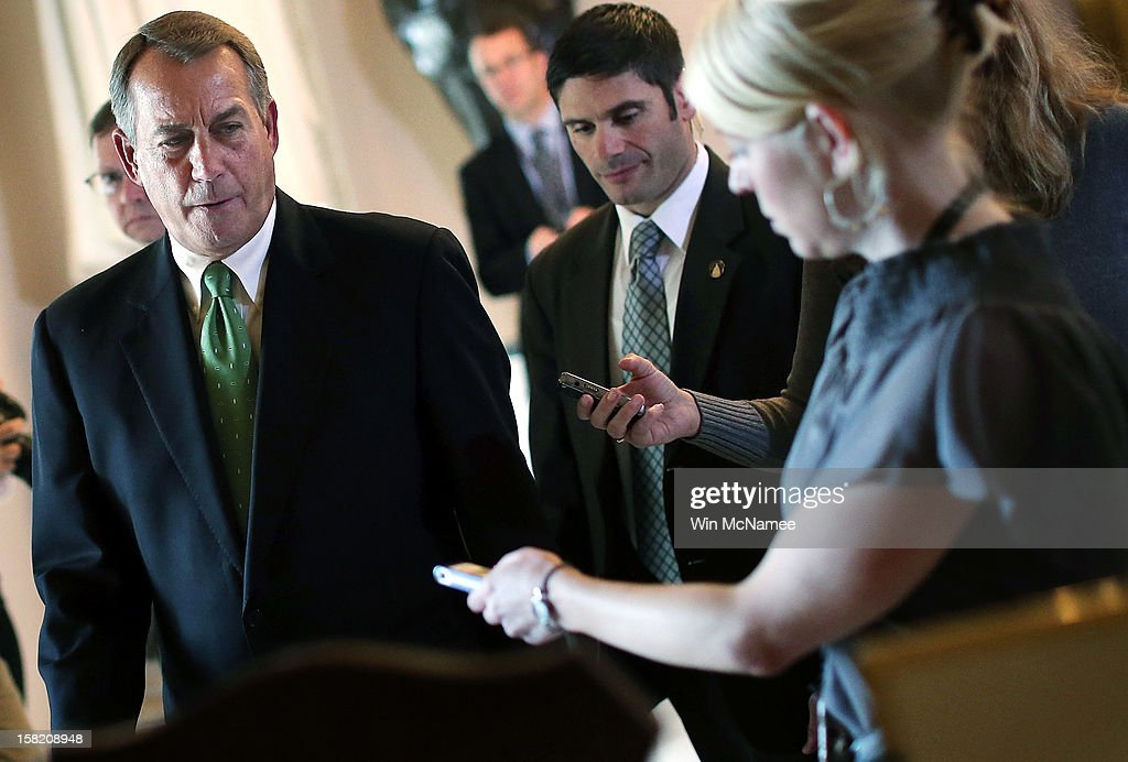 Followed by reporters, Speaker of the House <a gi-track='captionPersonalityLinkClicked' href=/galleries/search?phrase=John+Boehner&family=editorial&specificpeople=274752 ng-click='$event.stopPropagation()'>John Boehner</a> (R-OH) (L) walks to the House chamber to speak on the pending 'fiscal cliff' negotiations December 11, 2012 in Washington, DC. Congress and U.S. President Barack Obama's White House remain locked in a stalemate over the negotiations seeking a settlement to the fiscal crisis.