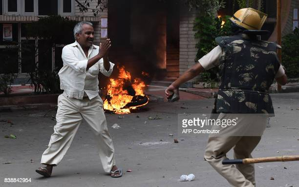 A follower of Indian religious leader Gurmeet Ram Rahim Singh pleads for his safety after being hit with a stick during clashes between the...