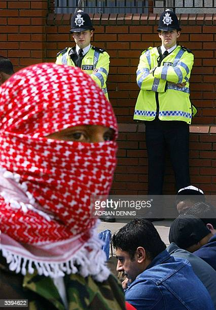 A follower of radical Cleric Abu Hamza al Masri walks past Metropolitan Police officers as Muslims pray on a residential street outside Finsbury Park...