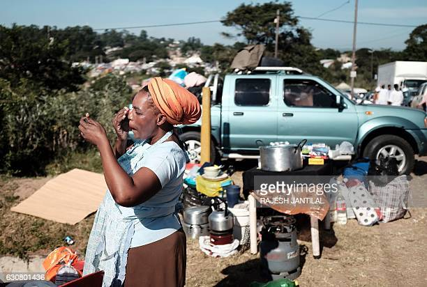 A follower of the Nazareth Baptist Church also known as the Shembe Church places a lotion to protect her face against the heat of the sun as she...