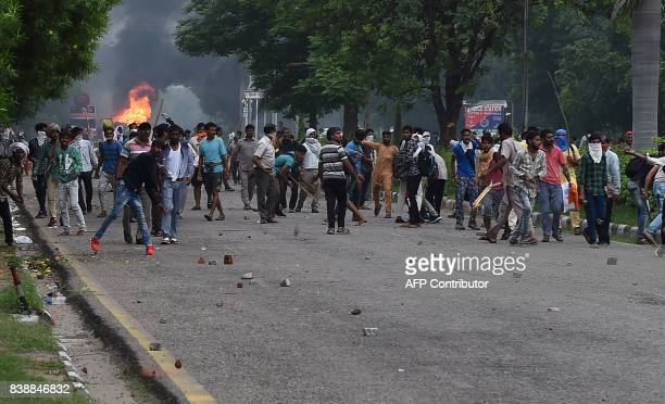 Followers of Indian religious leader Gurmeet Ram Rahim Singh throw stones at security forces during clashes after the controversial guru was...