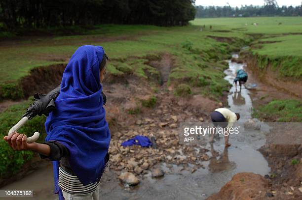 Followers of the Ethiopian Orthodox church walk on August 17 2010 in the source of the Blue Nile in northern Ethiopia a sparkling stream at Gish Abay...